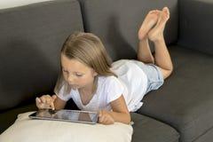 说谎在家庭客厅沙发的年轻美好和愉快的小女孩6或7岁横卧使用互联网数字式片剂触摸板 免版税库存照片