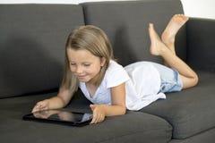 说谎在家庭客厅沙发的年轻美好和愉快的小女孩6或7岁横卧使用互联网数字式片剂触摸板 图库摄影