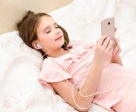 说谎在床上和听到音乐的逗人喜爱的女孩使用s 免版税库存图片