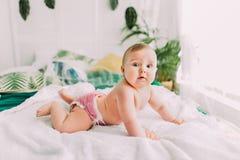说谎在床上和看照相机的逗人喜爱的婴孩的旁边porttrait 图库摄影
