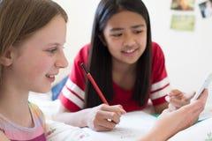 说谎在床上的两个女孩使用手机帮助与家庭作业 库存照片