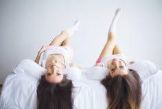 说谎在床上的两名惊人的妇女,当他们的头发掉下 免版税库存照片