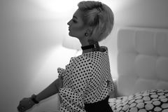 说谎在床上的可爱的引诱的年轻白肤金发的妇女在卧室,灰色极谱photoshoot 库存照片