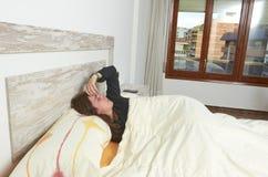 说谎在床上的妇女被激怒,当他们听见闹钟 e 库存照片