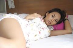 说谎在床上的年轻可爱和美丽的亚裔妇女在卧室摆在性感在秀丽户内演播室集合 免版税库存照片
