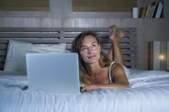 说谎在床上的年轻时髦的可爱和美丽的白种人妇女30s在晚上在家庭卧室使用互联网在便携式计算机 库存照片