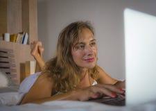 说谎在床上的年轻时髦的可爱和美丽的白种人妇女30s在晚上在家庭卧室使用互联网在便携式计算机 免版税库存照片