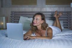 说谎在床上的年轻时髦的可爱和美丽的白种人妇女30s在晚上在家庭卧室使用互联网在便携式计算机 免版税库存图片