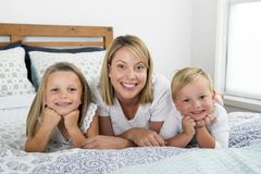 说谎在床上的年轻白肤金发的白种人妇女与她小的甜点3和7岁一起儿子和女儿微笑嬉戏和机会 免版税库存图片