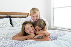 说谎在床上的年轻白肤金发的白种人妇女与她小的甜点3和7岁一起儿子和女儿笑的使用愉快 库存照片