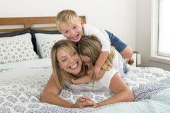 说谎在床上的年轻白肤金发的白种人妇女与她小的甜点3和7岁一起儿子和女儿笑的使用愉快 免版税库存图片