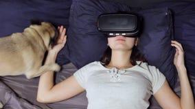 说谎在床上的枕头的年轻女人顶视图使用虚拟现实,手表VR录影 股票视频