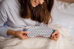 说谎在床和拿着上的微笑的妇女一个逗人喜爱的睡眠面具 免版税图库摄影