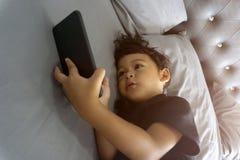 说谎在床和观看的戏剧上的亚洲泰国孩子在智能手机 库存照片