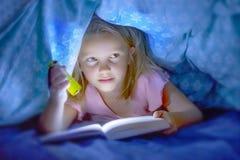 说谎在床罩在黑暗的阅读书下的美好的美好和相当小的白肤金发的儿童女孩6到8岁与火炬fla 免版税库存图片