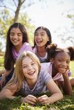 说谎在彼此的四位女小学生在领域,关闭  库存照片