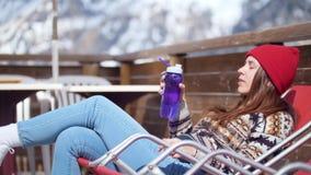 说谎在懒人和饮用水的一名年轻俏丽的妇女从塑料瓶 影视素材