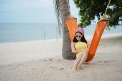 说谎在摇篮的妇女在海滩 免版税库存照片