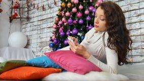 说谎在明亮的枕头在圣诞树附近和听到音乐的可爱的浅黑肤色的男人 非常规的圣诞节 股票录像