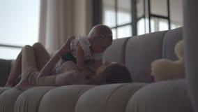 说谎在有女婴的沙发的逗人喜爱的亭亭玉立的年轻女人 在家使用与她的孩子的母亲 r 影视素材