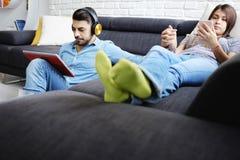 说谎在有片剂个人计算机和耳机的沙发的夫妇 库存照片