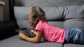 说谎在有片剂的沙发的女婴 小女孩说谎的使用在片剂 影视素材