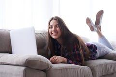 说谎在有膝上型计算机的沙发的轻松的女孩 免版税库存图片