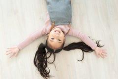 说谎在木地板上的女孩 免版税库存照片