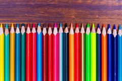说谎在木板的五颜六色的铅笔 免版税库存照片