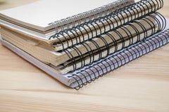 说谎在木桌上的堆不同的笔记本 免版税库存照片