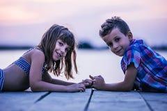 说谎在木码头和握手的孩子 图库摄影