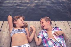 说谎在木码头和握手的孩子 免版税库存照片