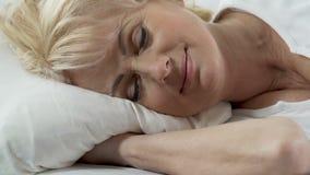 说谎在枕头,在她的面孔的轻的微笑,未受干扰的睡眠的资深妇女头 股票视频