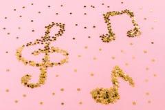 说谎在桃红色淡色背景的满天星斗的金黄五彩纸屑音符  免版税图库摄影
