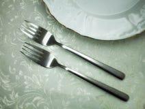 说谎在桌上的两把金属叉子在金渐近的板材旁边 免版税库存照片