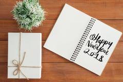 说谎在棕色木背景的运转的书桌和giftbox平的位置视图照片有新年好愿望笔记本的 库存图片