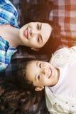 说谎在毯子和看在照相机的少妇和女孩垂直的画象  他们微笑着 女孩美丽 免版税库存照片