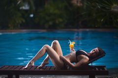说谎在水池背景的太阳懒人在夏天户外和在她的手上的女孩拿着橙汁 库存照片