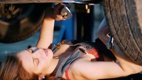说谎在汽车下和修理它的性感的技工女孩 关闭 影视素材