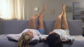 说谎在沙发和保持脚的两花姑娘,明显地被刮的腿 股票视频