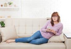 说谎在沙发和在家使用智能手机背景的中年妇女 复制空间并且嘲笑  网上购物,互联网 免版税库存图片
