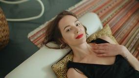 说谎在沙发和微笑对照相机的年轻俏丽的深色的妇女画象  免版税库存照片