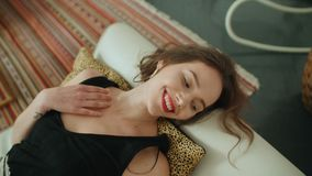 说谎在沙发和微笑对照相机的年轻俏丽的深色的妇女画象  库存照片