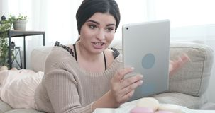 说谎在沙发的妇女使用视频聊天的数字片剂 影视素材
