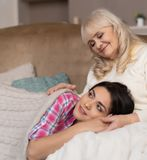 说谎在沙发的母亲的膝盖的迷人的女孩 库存照片