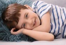 说谎在沙发的逗人喜爱的小男孩 免版税库存照片