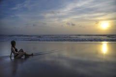 说谎在沙子的少妇剪影看对海与美丽的太阳的日落天际 免版税库存照片