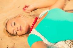 说谎在沙滩的妇女放松在夏天期间 库存照片