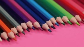 说谎在波浪的桃红色背景的许多不同的色的铅笔 股票视频