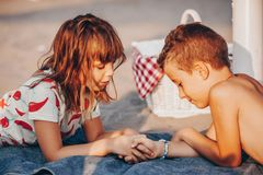 说谎在海滩和握手的孩子 库存图片